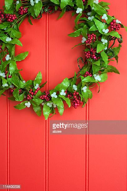 mistletoe and berry wreath on red panelled background - what color are the berries of the mistletoe plant stock pictures, royalty-free photos & images