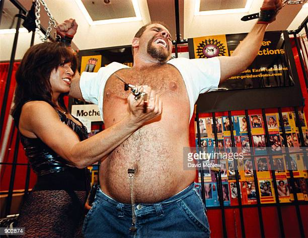 Mistress Lee inflicts pains upon Chris Devicarlis by using a knife to flick metal clamps from his skin at the Erotica LA convention June 11 1999 in...