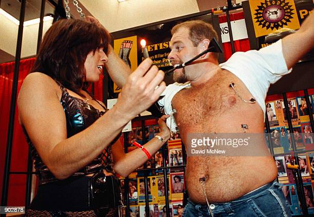 Mistress Lee prepares to pour hot wax from a candle onto the skin of Chris Devicarlis at the Erotica LA convention June 11 1999 in Los Angeles...