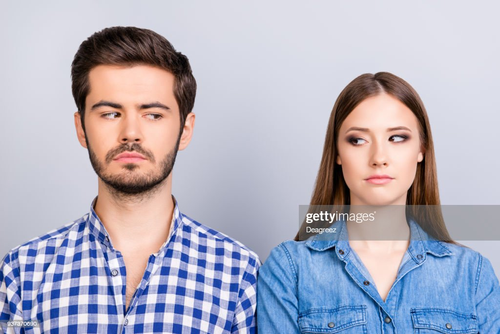 Mistrust and cheat problems. Annoyed couple is ignoring each other, but spy each other secretly, they stand on pure background in casual shirts : Stock Photo