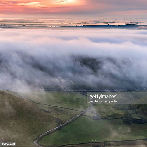 Misty covered hills with a golden sky. Peak District National park. UK. Europe.