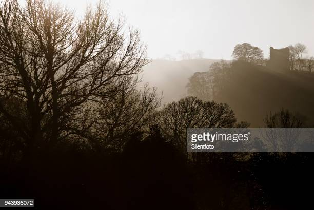 misty landscape with english castle on hill - peveril castle stock pictures, royalty-free photos & images