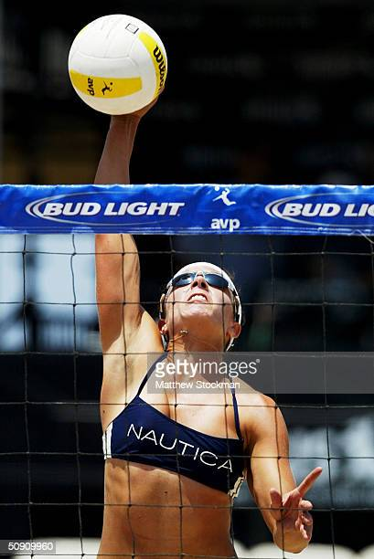 Misty May spikes the ball against Heather Lowe and Jenny Pavley during the Bud Light Huntington Beach Open on May 29 2004 in Huntington Beach...