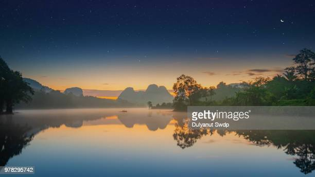 misty morning at lake in krabi province, south of thailand. - tropical island sunset stock pictures, royalty-free photos & images