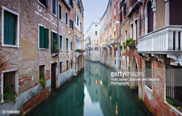misty morning reflections along canal in venice, italy - canale grande venedig stock-fotos und bilder
