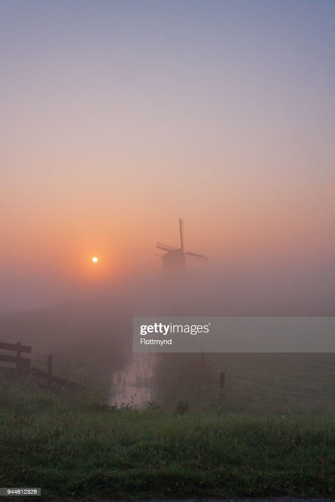 Misty morning sunrise with silhouette of a windmill : Stock Photo
