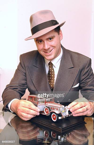 ANDREJ HERMLIN SWING DANCE ORCHESTRA LEITER MUSIKER SWING MUSIC BERLIN mit Automodell einer Limousine aus den 30er swing Jahren der USA gekleidet in...