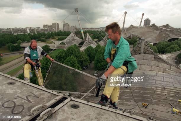 Mit Bergsteigerausrüstung gesichert, montieren zwei Fassadentechniker am 18.6.1997 die Acrylglasplatten auf dem Münchener Olympiadach ab. Nach 25...