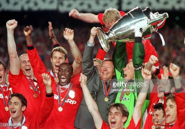 Mit dem Pokal feiert die Mannschaft von Manchester United am 2651999 im Nou CampStadion in Barcelona ihren Sieg im Finale der Champions League In der...