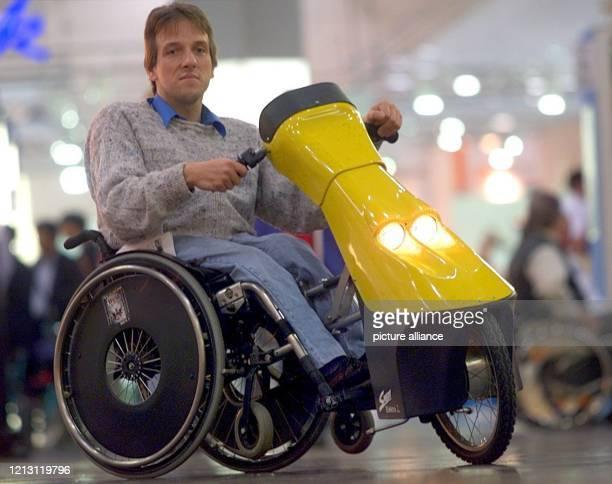 Mit einem vom Elektromotor angetriebenen Vorsatz für seinen Rollstuhl bewegt sich Messebesucher Michael Schmidt am in Düsseldorf über die Messe...