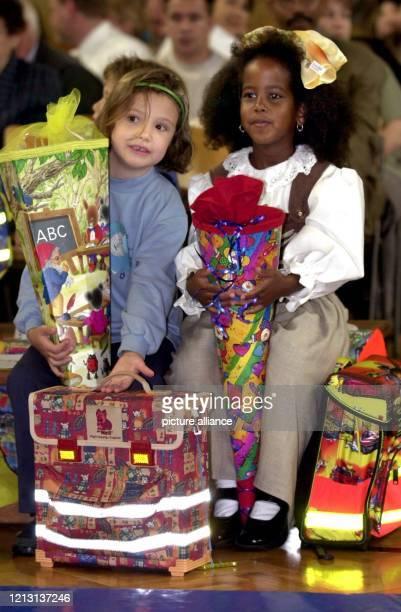 Mit einer großen Schultüte im Arm sitzen die sechsjährige Miriam und die gleichaltrige Kochob am 882000 bei der Einschulungsfeier in der ersten Reihe...