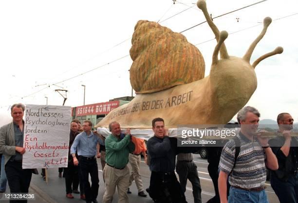 Mit einer meterlangen Schnecke aus Pappe, die den ihrer Ansicht nach zu langsamen Prozeß der Gesetzgebung illustrieren soll, ziehen am 14.5.1997 rund...