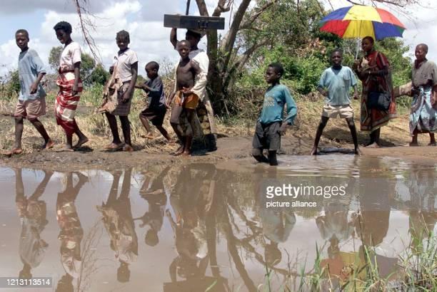 Mit ihren Habseligkeiten in den Taschen und einem Koffer auf dem Kopf läuft eine Familie am 732000 in der mosambikanischen Provinz Machanga über eine...