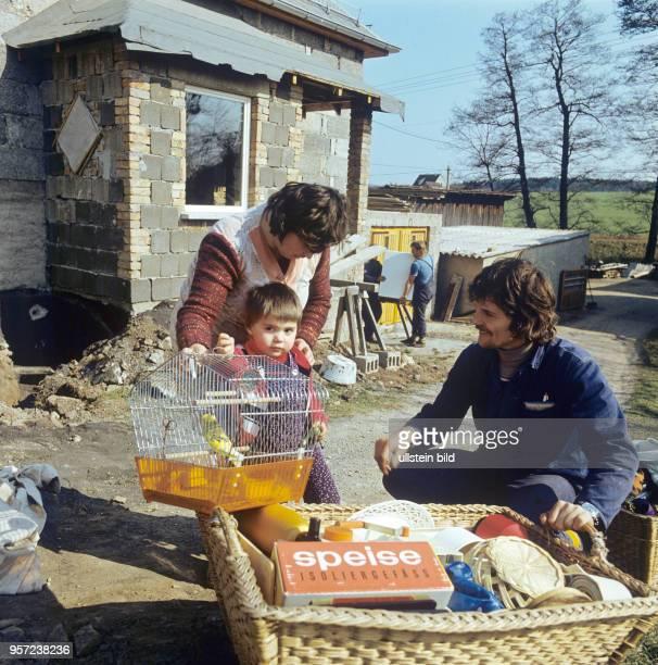 Mit Kind und Vogelkäfig zieht eine junge Familie in ein im Rohbau befindliches Eigenheim in der Gemeinde Frießnitz bei Gera undatiertes Foto von 1982...