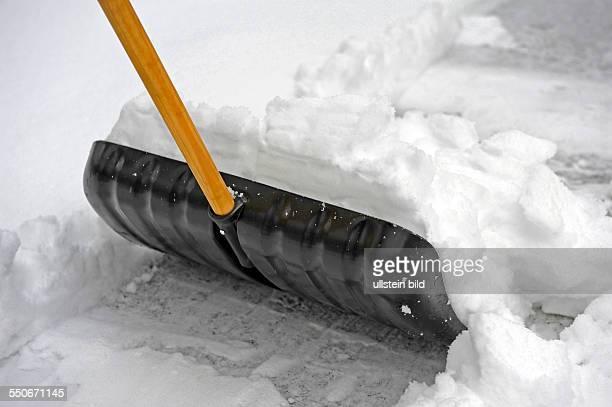Mit Schneeschieber Gehweg raumen