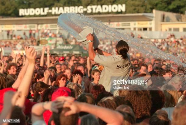 Mit Wasser zur Abkühlung überschüttet eine Sicherheitsmitarbeiter die Fans beim Wolfgang Petry Konzert am im Rudolf Harbig Stadion in Dresden