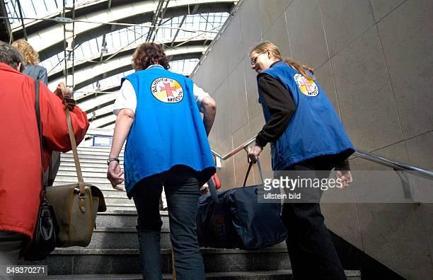 Mitarbeiter der Bahnhofsmission auf dem Bahnsteig Frau Ursula Czaika und ein FSJler sind Reisenden behilflich tragen Gepäck