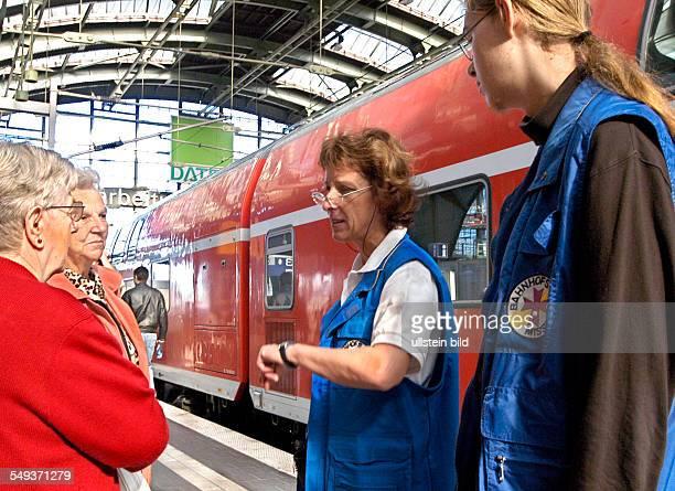 Mitarbeiter der Bahnhofsmission auf dem Bahnsteig Frau Ursula Czaika und ein FSJler sind Reisenden behilflich