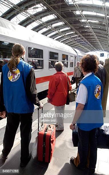 Mitarbeiter der Bahnhofsmission auf dem Bahnsteig Frau Ursula Czaika Mitarbeiterin und ein FSJler helfen Reisenden mit ihrem Gepäck beim Einsteigen