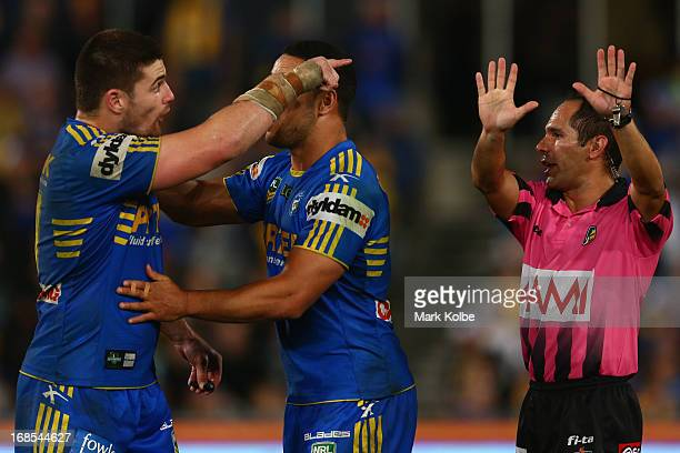 Mitch Allgood of the Eels is held back by Jarryd Hayne of the Eels as he gestures after referee Ashley Klein sends him to the sin bin for ten minutes...