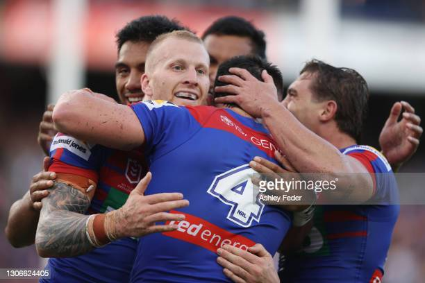 Mitch Barnett of the Knights celebrates his try with team mates during the round one NRL match between the Newcastle Knights and the Canterbury...