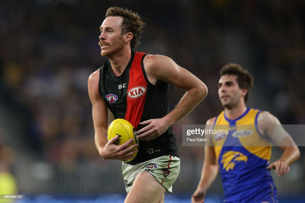 Mitch Brown of the Bombers looks to pass the ball during the round 14 AFL match between the West Coast Eagles and the Essendon Bombers at Optus Stadium on June 21, 2018 in Perth, Australia.