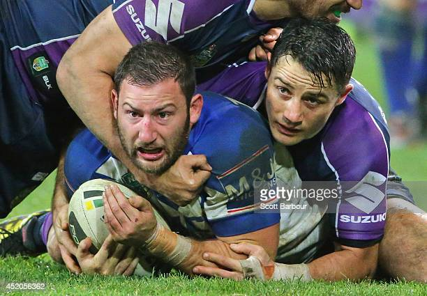 Mitch Brown of the Bulldogs is tackled by Cooper Cronk of the Storm during the round 18 NRL match between the Melbourne Storm and the Canterbury...