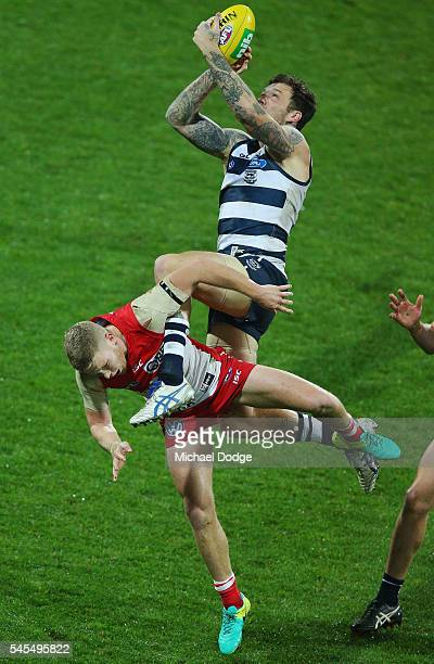 Mitch Clark of the Cats marks the ball over Daniel Hannebery of the Swans during the round 16 AFL match between the Geelong Cats and the Sydney Swans...