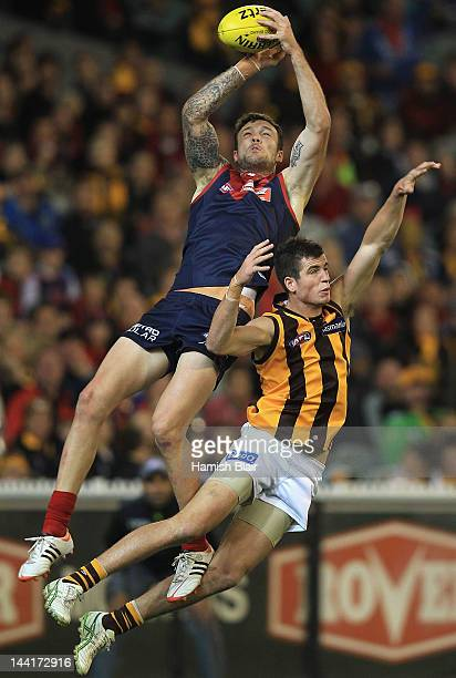 Mitch Clark of the Demons attempts to mark over Ben Stratton of the Hawks during the round seven AFL match between the Melbourne Demons and the...