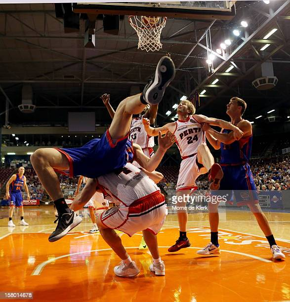Mitch Creek of Adelaide falls over Greg Hire of Perth during the round ten NBL match between the Adelaide 36ers and the Perth Wildcats at Adelaide...