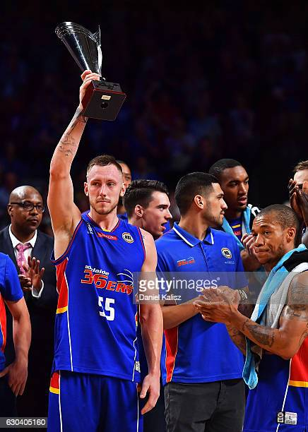 Mitch Creek of the Adelaide 36ers holds a trophy aloft after the round 12 NBL match between the Adelaide 36ers and the Perth Wildcats at Titanium...