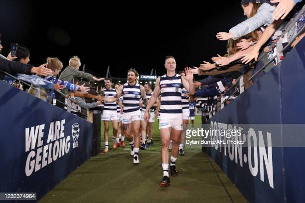 Mitch Duncan and Zach Tuohy of the Cats celebrate a win with fans during the 2021 AFL Round 05 match between the Geelong Cats and the North Melbourne...