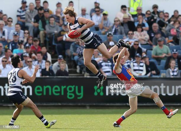 Mitch Duncan of the Cats collides with the ball over Pearce Hanley of the Lions during the round 23 AFL match between the Geelong Cats and the...