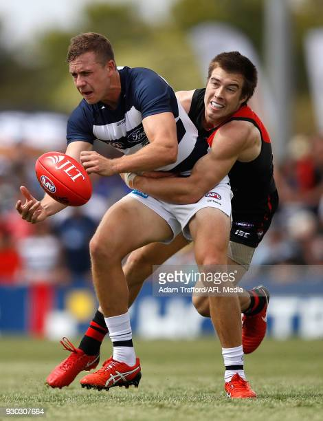 Mitch Duncan of the Cats is tackled by Zach Merrett of the Bombers during the AFL 2018 JLT Community Series match between the Geelong Cats and the...