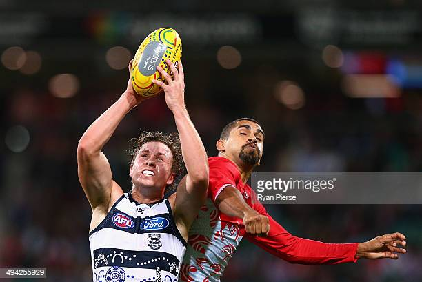 Mitch Duncan of the Cats marks in front of Lewis Jetta of the Swans during the round 11 AFL match between the Sydney Swans and the Geelong Cats at...