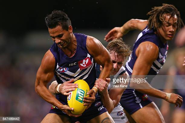 Mitch Duncan of the Cats tackles Danyle Pearce of the Dockers during the round 17 AFL match between the Fremantle Dockers and the Geelong Cats at...