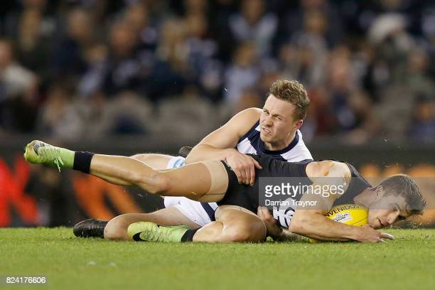 Mitch Duncan of the Cats tackles Marc Murphy of the Blues during the round 19 AFL match between the Carlton Blues and the Geelong Cats at Etihad...