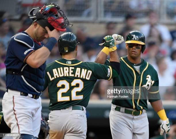 Mitch Garver of the Minnesota Twins looks on as Khris Davis of the Oakland Athletics congratulates teammate Ramon Laureano on a solo home run during...
