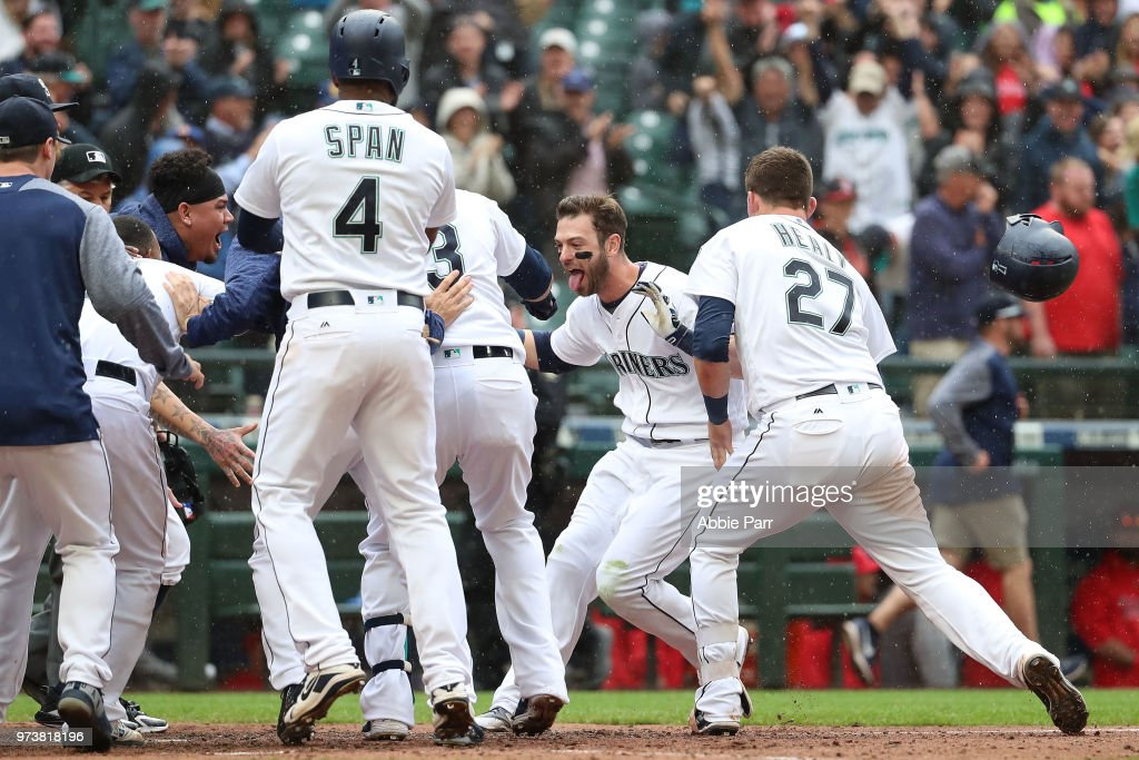 Mitch Haniger #17 of the Seattle Mariners celebrates with teammates after hitting the game winning two run home run in the ninth inning against the Los Angeles Angels of Anaheim during their game at Safeco Field on June 13, 2018 in Seattle, Washington.