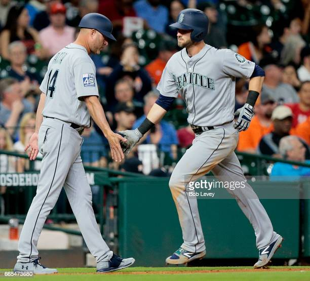 Mitch Haniger of the Seattle Mariners celebrates with third base coach Manny Acta fter hitting a home run in the third inning against the Houston...