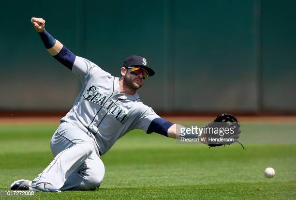 Mitch Haniger of the Seattle Mariners goes into a slide but watches the ball fall to the ground for a double off the bat of Matt Chapman of the...