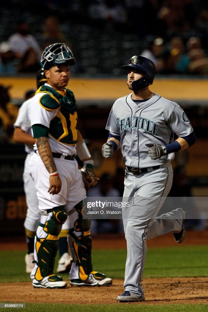 Mitch Haniger #17 of the Seattle Mariners runs past Bruce Maxwell #13 of the Oakland Athletics after hitting home run during the third inning at the Oakland Coliseum on September 25, 2017 in Oakland, California. The Seattle Mariners defeated the Oakland Athletics 7-1.