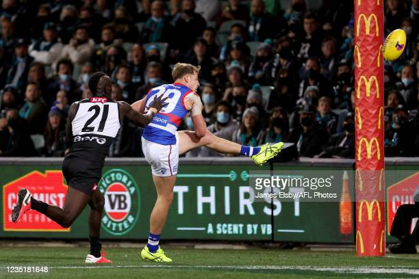 Mitch Hannan of the Bulldogs kicks a goal in front of Aliir Aliir of the Power during the 2021 AFL Second Preliminary Final match between the Port...