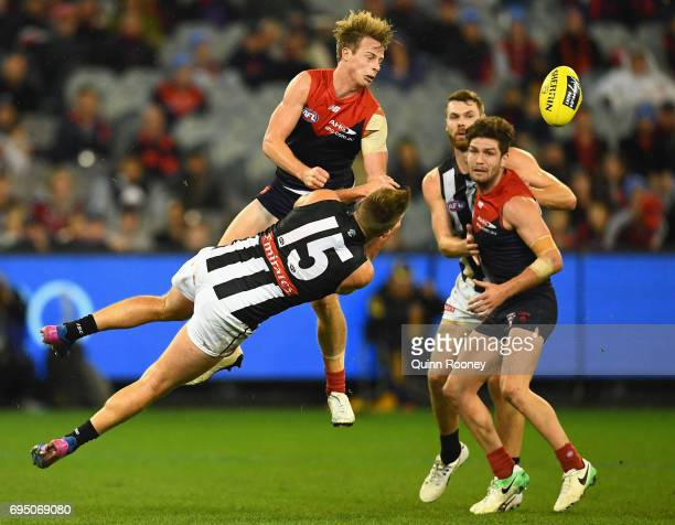 Mitch Hannan of the Demons and Lynden Dunn of the Magpies collide while going for a mark during the round 12 AFL match between the Melbourne Demons...