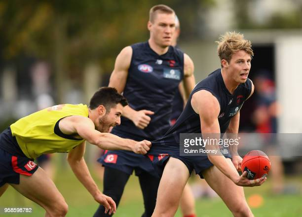 Mitch Hannan of the Demons handballs whilst being tackled by Alex NealBullen during a Melbourne Demons AFL training session at Gosch's Paddock on May...