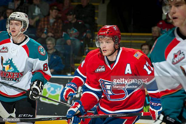 Mitch Holmberg of the Spokane Chiefs skates between Colten Martin and Damon Severson of the Kelowna Rockets during second period on March 5, 2014 at...