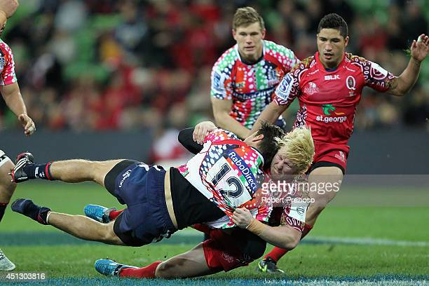 Mitch Inman of the Rebels is tackled by Beau Robinson of the Reds during the round 17 Super Rugby match between the Rebels and the Reds at AAMI Park...