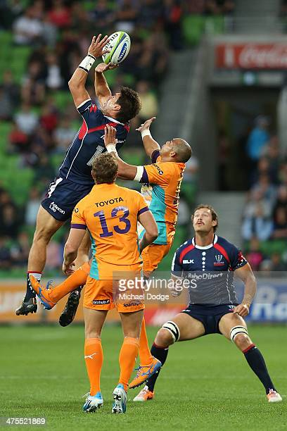 Mitch Inman of the Rebels palms the ball dowon to Scott Higginbotham away from Cornal Hendricks of the Cheetahs during the round three Super Rugby...