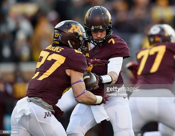 Mitch Leidner of the Minnesota Golden Gophers hands the ball to teammate Shannon Brooks during the first quarter of the game against the Wisconsin...