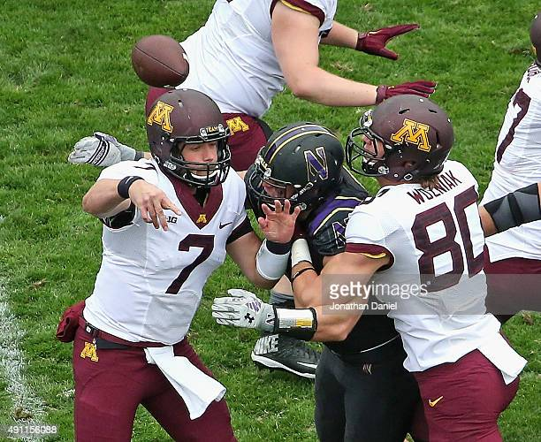 Mitch Leidner of the Minnesota Golden Gophers is hit as he throws by Dean Lowry of the Northwestern Wildcats as Nate Wozniak tries to hold Lowery off...